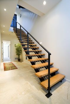 This modern staircase has a metal frame with natural wood treads. The stone tile floor blends seamlessly together. Stair Railing Design, Home Stairs Design, Staircase Railings, Interior Stairs, Modern House Design, Spiral Staircases, Modern Stairs Design, Flur Design, Hall Design