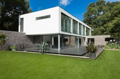 Architecture: Amazing Eco Friendly Home Architecture Equipped With White Walls And Stone Fence With Glass Window As Well As Spacious Green Yard Charming White Details Dominate Impeccable Minimalist Home in Germany Or Architecture