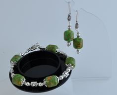 http://www.adhicreations.com/products/372-turquoise-green-beauty.aspx  Turquoise Green Beauty  Gorgeous gemstone Bracelet and earrings set made of lovely Mosaic Turquoise beads. The drum shaped beads have lovely green and brown combination. The antiqued silver finish beads add beauty to the Jewelry. Make it a lovely 3-piece set by adding the coordinated necklace from below.  $15  www.adhicreations.com