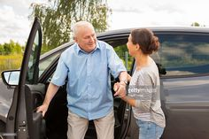 Stock Photo : Caregiver helping senior out of the car