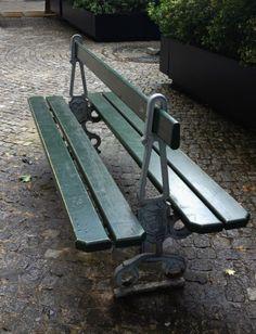 a green park  bench on the cobblestones in Paris FleaingFrance