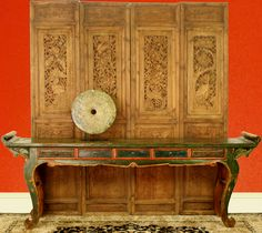 A beautiful Green Antique Chinese Altar Table with heavily carved antique courtyard screens as a wall treatment.