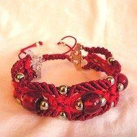 Náramek je z lesklé saténové šnůrky a matné bavlněné příze. Ozdobu tvoří 3 velké červené korálky a jednoduché stříbrné kuličky.