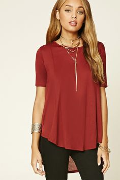A knit tee featuring a trapeze silhouette, a slight high-low hem, round neckline, and short sleeves.
