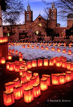 Christmas eve luminarias in the plaza of Old Town Albuquerque, New Mexico. San Felipe de Neri church in background.