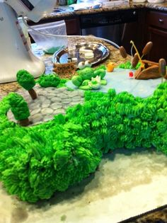 fishing cake.  Kidney shaped cake I hand carved to shape.  fondant hand made without molds of frog, trees, boat, cat tails, cobblestone and pond.