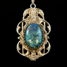 Detailed Art Nouveau styling on this pendant necklace includes two cranes and arched flourishes around a huge central dichroic cabochon in peacock colors. Iridescent emerald green, royal blue and copper reflect from a layer beneath clear glass. Each dichroic stone was different because of this layering process. This necklace is not only nature-inspired, but also one-of-a-kind.