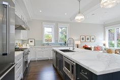 Amazing two-tone kitchen with soft gray walls paint color, Blanco faucet & sink, creamy white kitchen cabinets, charcoal gray blue kitchen island, calacatta ora marble countertops, sink in kitchen island and Ann Sacks - Michael S Smith Labyrinth Tiles backsplash.    Benjamin Moore Balboa Mist