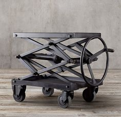 RH's Industrial Scissor Lift Table:We've reproduced and repurposed an early 20th-century American factory jack as a bold, industrial table with uncommon functionality. Crafted of heavy sheet metal, it's set on casters and powered by a big wheel to lift or lower.