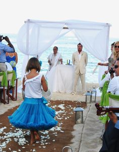 A cute little girl was throwing rose white petals while walking down the aisle.