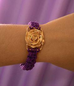 Pulseira em macramê roxo com flor dourada.
