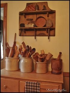Primitive shelf with collectables& old crocks filled with prim mashers, rolling pins, & spoon..