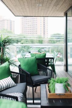 This black and green covered patio features black wicker chairs accented with dark gray seat cushions and kelly green pillows placed on a black striped rug at a black slatted top coffee table.
