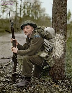 Private K.O. Earl holding his Lee-Enfield, of the Perth Regiment, stops for a rest in the forest north of Arnhem, as the 5 Canadian Division advances. 15 April 1945, Arnhem, The Netherlands.