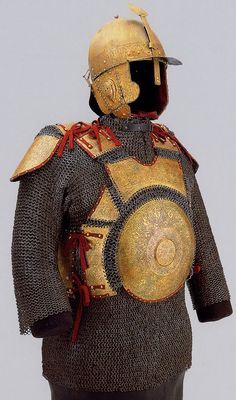 Ottoman Chichak type helmet with krug (chest armor) worn over a zirah (mail shirt), 16th c, gold-plated iron, embossed with decorative etchings of arabesques and Arabic inscriptions (prayers to Allah and verses from the Qur'an). Parts of the armour are attributed to a Mamluk prince because of its similarity to the helmet of Khairbak, the governor of Aleppo, who rendered Syria in 1517 to Selim I Sultan of the Ottoman Empire. Kunsthistorisches Museum, Vienna.