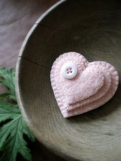 A pink heart brooch made from recycled wool from garments and a vintage glass button.
