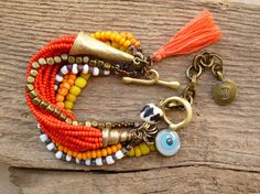 Gypsy Bohemian Multi strand beaded bracelet by BeadStonenSkin, 16 strand bracelet with seed beads in orange, red and yellow colors - yellow beads are glass, handmade from Indonesia, one strand with square brass spacers,  African batik bone bead, a white and dark distressed glass seed beads strand, two brass cones, toggle clasp handmade, evil eye and the orange tassel, antique brass chain with a brass charm attached. 17 cm
