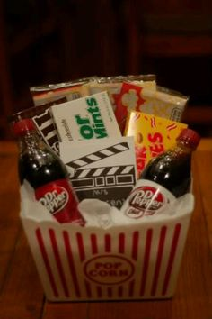 Movie night in basket: Romantic Movie Dvd (Like The Notebook), Marriage Comedy DVD, bags of popcorn, candy, soda