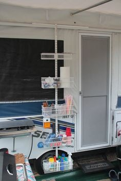 Camping DIY:  Shelves on the outside of the Pop up camper    We did a long track to hang 2 verticals, 1 has the shelf bracket with a vinyl shoe shelf organizer hanging from it to easily grab shoes, but I might have to try this too!