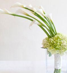 bouquet d'arums blancs et de têtes d'hortensia, un jolie manchon blanc satiné recouvre les tiges des fleurs.