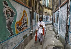 """A Hindu priest walks in an alley with painted walls depicting a traditional Indian wrestling training centre called """"Akhaara"""", in Kolkata November 17, 2014. (REUTERS/Rupak De Chowdhuri)"""