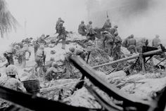 Marines attack heavily armed Japanese pillbox on Tarawa, Gilbert Islands by climbing on top and shootting down in 11/21/43