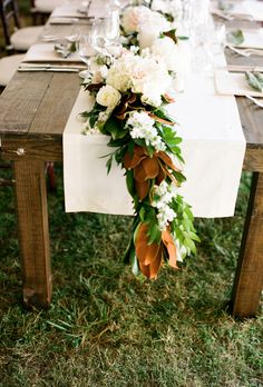 This lovely runner, created by Tennessee-based floral studio The Enchanted Florist, pays tribute to the southern reception space. Classic magnolia flowers, combined with white roses, hydrangeas, and greenery, top wooden farm tables.