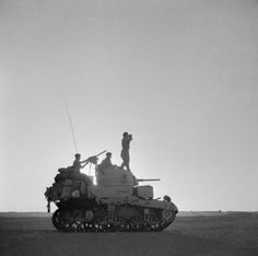 A Stuart tank is silhouetted against the setting sun as its commander scans the horizon, 6 September 1942.