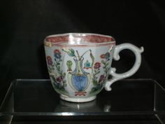 A EARLY WORCESTER HEXAGONAL COFFEE CUP C.1756 / 58  £146 SCROLL HANDLE,THE CUP PAINTED WITH FLOWERS ORIENTAL VASES AND INSECTS WITH A INNER CROSS HATCHED BORDER UNMARKED FOR A SIMILIAR TEA BOWL AND SAUCER IN THIS EARLY PATTERN SEE WORCESTER PORCELAIN BY S SPERO IN THE ZORENSKY COLLECTION PAGE 94 FIG 47.CONDITION CRACKED AND CHIPPED AND REPAIRED BY COPPER RIVETS O/A SISE 2 1/8 TH INCHES TALL