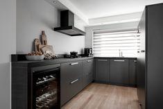 Een donkergrijze keuken met witte wanden, zwarte apparatuur en een licht houten vloer. Voorzien van wijnkoelkast van Miele en een Fusion Vulcano wokbrander.
