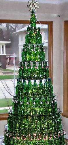 Stacked Green Bottles on Circles of Glass To Form a Bottle Christmas Tree
