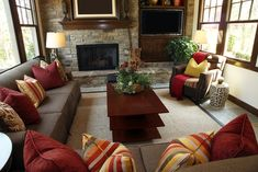 Rustic living room design with brick wall containing a fireplace and television.  Brown sofas are decorated with red, orange and yellow pillows.
