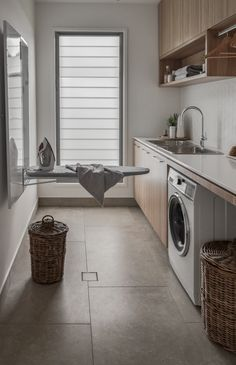 Designing the ultimate laundry, all the tips and tricks you need! Luxury laundry with ironing centre built into the wall. Timber cabinetry and sleek finishes