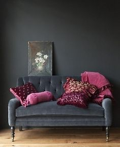 Gray walls, gray velvet tufted sofa, mauve mulberry amethyst pillows and throw