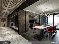 惹雅設計以大刀闊斧的「十字軸線」概念,規劃 75 坪大宅,以輕奢元素注入現代空間,由玄關延伸的長廊成為貫穿屋案的主軸,平均分配左側的視聽起居功能與右側為餐廚空間,打造了獨特的公私領域交疊設計。巧妙運用長廊天花格柵、雕刻白石紋與鏡面,打造無限延伸的視覺感受,並利用灰玻、黑玻和大理石收邊,增添豪邸的精緻