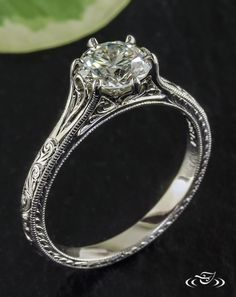 Six Prong Scroll Engagement RingThis platinum scroll engraved engagement ring features a round brilliant diamond in a 6 prong setting that is intertwined with filigree curls.#Ido #GreenLakeMade #EngagementRing