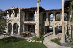Backyard Exterior: Mediterranean, Tuscan, European architecture, stucco, smooth stucco, balcony, wrought iron, decorative iron, tile roof, stucco chimney, detailed fascia, wood windows, wood casement windows, wood French doors, French door, arch widow, arch wood casement windows, outdoor lighting, custom wood garage door, pillars, stone exterior walls, stucco walls, wood walls, upstairs balcony, balcony wrought iron railing, title roof, landscaping.