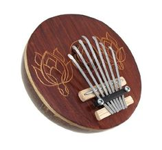 Hand Carved Coconut Karimba Mbira Thumb Piano by Things2Die4. $19.99. This beautifully crafted Karimba (also known as a kalimba, Mbira or Thumb Piano) is hand made from half a coconut shell with a beautiful wooden face, hand-carved with the image of a butterfly, lizard, or turtle. Metal keys are suspended above the acoustic chamber and when plucked with the fingers or thumbs make a delightfully rich sound. This gorgeous mbira is great for use as a decoration, and m...