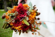 ovely combination of terra cotta roses, orange mums, seeded eucalyptus, green millet grass, acorns on the branch and bittersweet berries