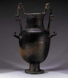A GREEK BLACK-GLAZED NESTORIS   South Italy, Circa Mid 4th Century B.C.   Ovoid in form, with the characteristic vertical handles rising from the shoulders to the rim and decorated with disks  19¼ in. (48.9 cm) high