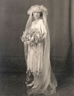 1920s bride wearing a street length dress, big headpiece and long train.  And, her flowers with long streamers are gorgeous!