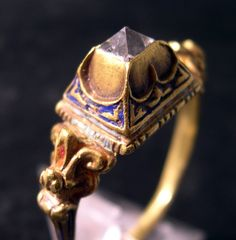 Gold and diamond Renaissance ring. The rectangular bezel is set with a pyramid-cut diamond in a raised collet. The slender hoop terminates at the shoulders in volutes, pierced and enamelled with well frosted orange. The sides of the bezel are chased in the upper part with crescents, panels below filled with bleu enamel, the joints forming claws. Late 16th century