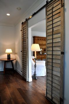 Love the louvered doors used for an interior barn-door setup.  Beautiful patina.