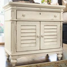 """Nightstand with a pull-out shelf and two louvered doors.  Product: Nightstand   Construction Material: Wood   Color: Linen    Features: Two adjustable shelves behind two louvered doorsOne drawer and one pull-out shelfDistressed finishDimensions: 30"""" H x 30"""" W x 18"""" D"""