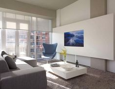 télé murale encadrée, canapé en tissu gris clair et tapis shaggy assorti
