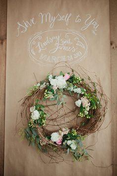 Décoration entrée sur fond de papier kraft avec logo des mariés en écriture blanche + couronne de fleurs