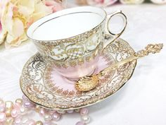 Find a nice cozy spot and enjoy the simple pleasure of a hot cup of tea in this stunningly elegant pink Royal Stafford English bone china tea set that includes 1 teacup, and 1 saucer. Features bright gold lace filigree accents over a crisp white glaze surrounded soft pink. Gold trim gleams brightly and adds that special elegance and charm to any table setting. Would make a lovely addition to any collection.  Made in England, this tea set and can be used for tea parties, weddings, formal…