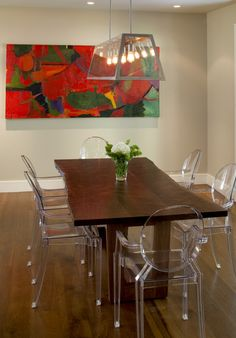 Lucite chairs and bold art in a modern dining room.