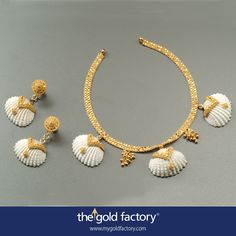 Cockle shells crowned with intricate gold lace borders, each inlaid with a single gold motif, are lined all in a row interspersed with little ball clusters and strung on a double x-phul chain in this thoroughly beautiful necklace from our Ocean's Jewels Collection. With matched detachable earrings, everything in hallmarked 22K gold.  Necklace : 12 gm, ~ Rs.43300/- Earrings : 5 gm, ~ Rs.18200/-