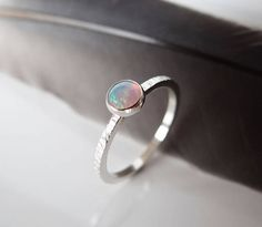 Hand crafted Opal stacking ring in Sterling Silver, custom made in your size. A 5mm Opal Cabochon stone is bezel set onto a slim band of Sterling Silver, which I hand texture with a tree bark pattern on its outer edge. This ring forms part of my birthstone stacking rings